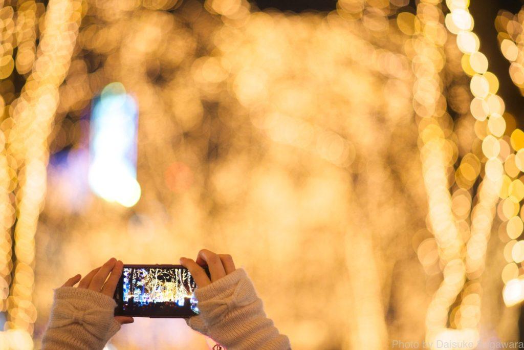 スマホで光のページェントを撮っている人